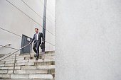 Businessman on his way to work. He is dressed in a formal suit and is walking down some steps.