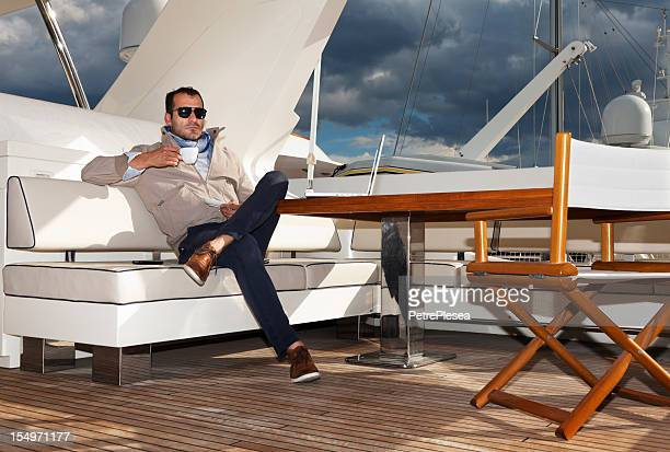 Businessman on the yacht drinking coffee and relaxing