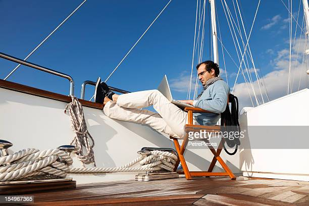 A businessman on the yacht texting and reading emails