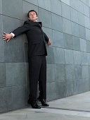 Businessman on tip toes, back against wall, arms outstretched, looking up