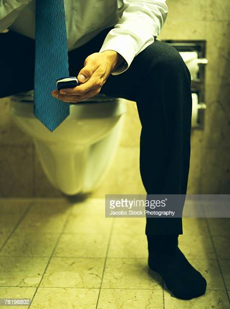 Businessman on toilet with cellphone