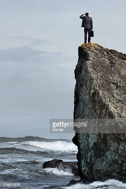 Businessman on top of cliff looking out to sea