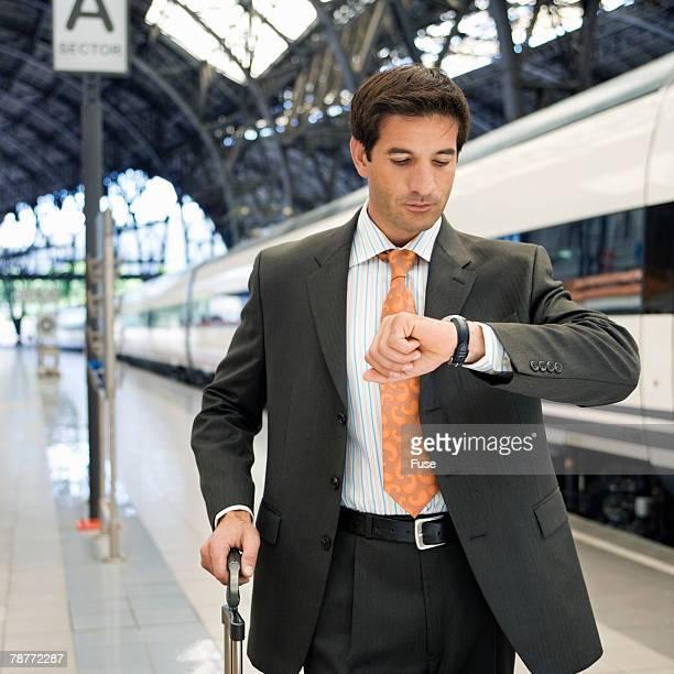 Businessman on Train Platform Checking the Time