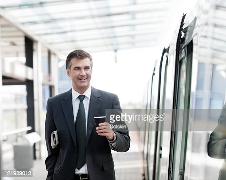 businessman on train station, holding coffee : Stock Photo