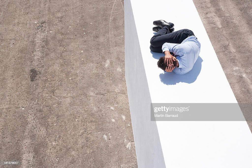 Businessman on wall outdoors in fetal position
