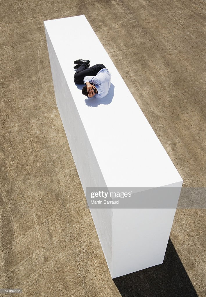 Businessman on wall outdoors in fetal position : Stock Photo