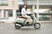 Image of a young businessman going at work on the scooter