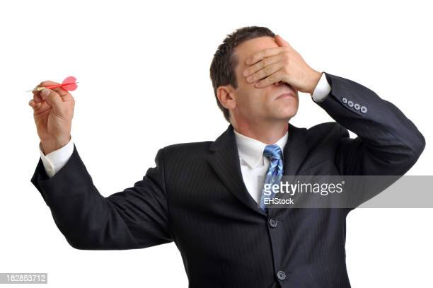 Businessman on white throwing dart with hand over eyes