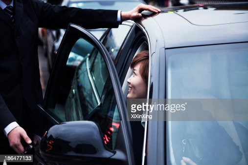 Businessman opening car door for businesswoman during the day in Beijing