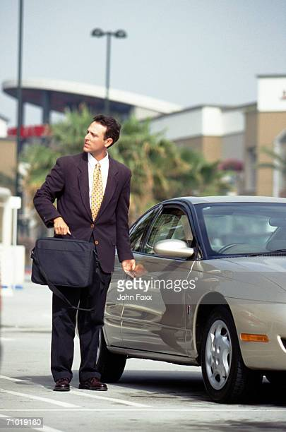 Businessman opening car door, looking away