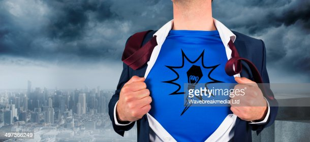 Composite image of businessman opening his shirt superhero style : Stock Photo