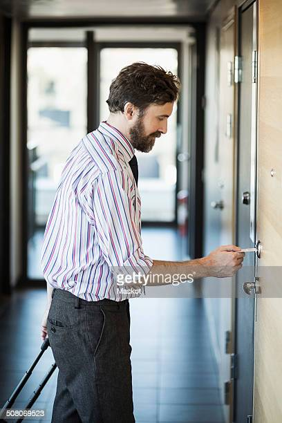 Businessman opening hotel door with cardkey