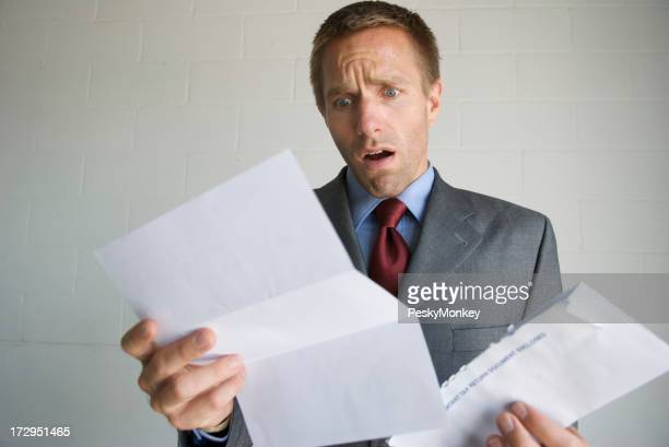 Businessman Opens Letter with Expression of Disbelief