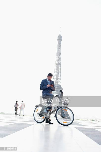 Businessman operating a mobile phone on a bicycle with the Eiffel Tower in the background, Paris, Ile-de-France, France