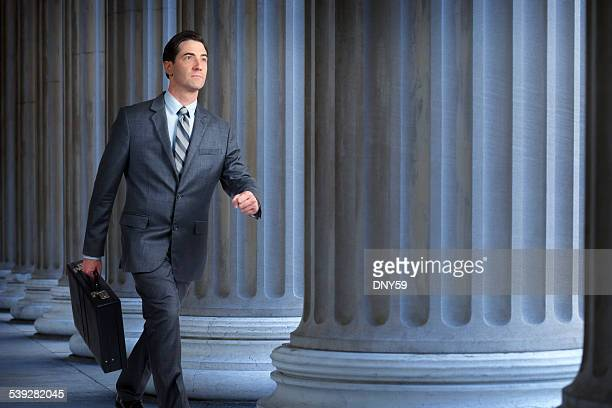 Businessman or lawyer walking past a row of columns