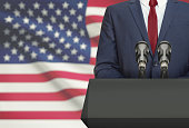 Businessman or politician making speech from behind the pulpit with national flag on background - United States