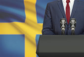 Businessman or politician making speech from behind the pulpit with national flag on background - Sweden
