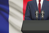 Businessman or politician making speech from behind the pulpit with national flag on background - France