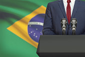 Businessman or politician making speech from behind the pulpit with national flag on background - Brazil