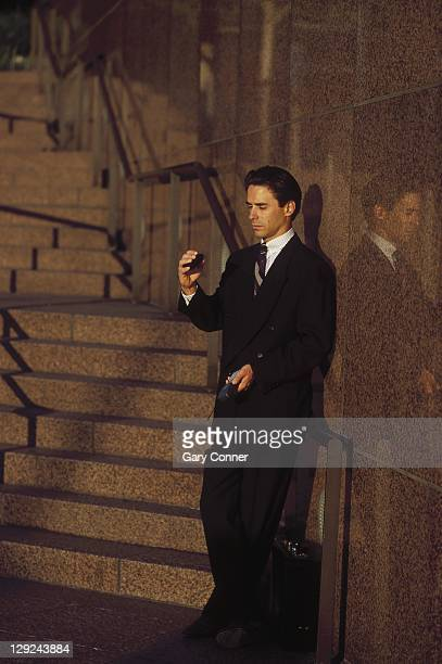 Businessman outdoors checking pager