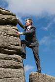 Businessman Scales a Big Rock