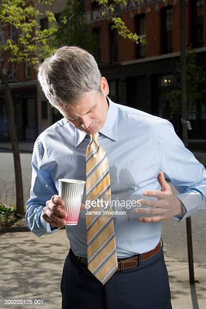 Businessman outdoors, coffee spilt on shirt