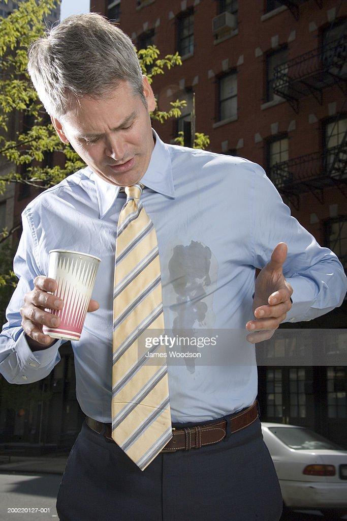 Businessman outdoors, coffee spilt on shirt
