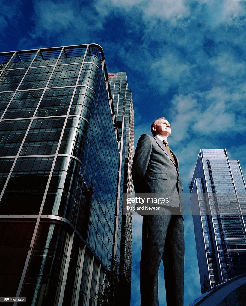 Businessman outdoors, hands clasped behind back, low angle view : Stock Photo