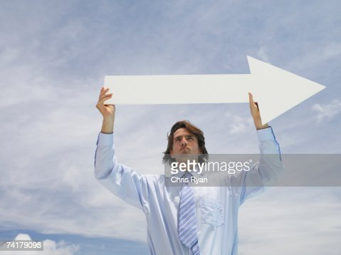 Businessman outdoors holding blank arrow with sky in background : Stock Photo