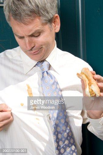 Businessman outdoors, hotdog sauces spilt on shirt, close-up