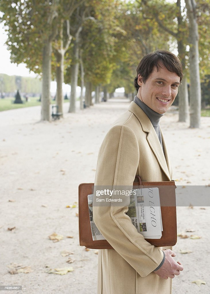 Businessman outdoors in park with newspaper : Stock Photo