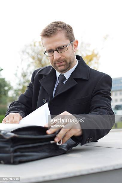 Businessman outdoors looking at document