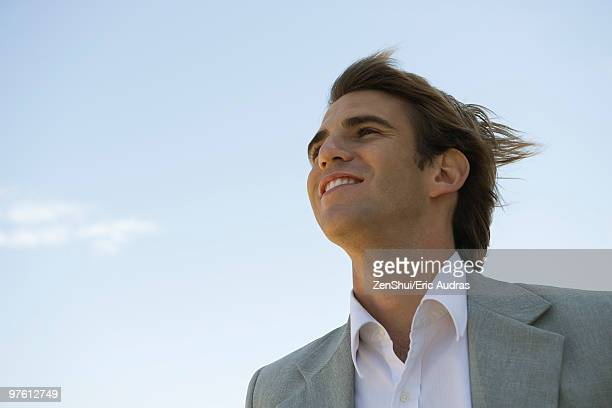 Businessman outdoors, looking away optimistically