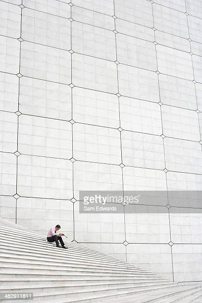 Businessman outdoors on staircase reading newspaper