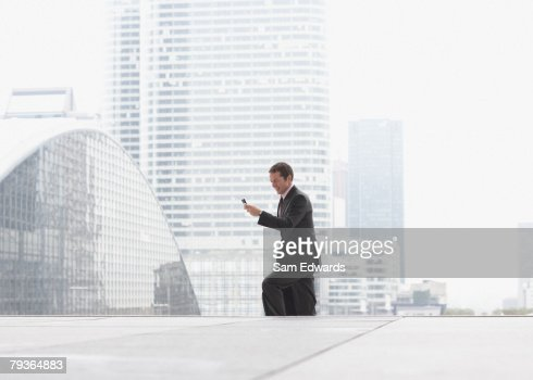 Businessman outdoors on staircase with cellular phone