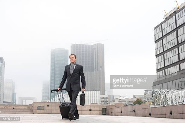 Homme d'affaires à pied avec bagages à l'extérieur