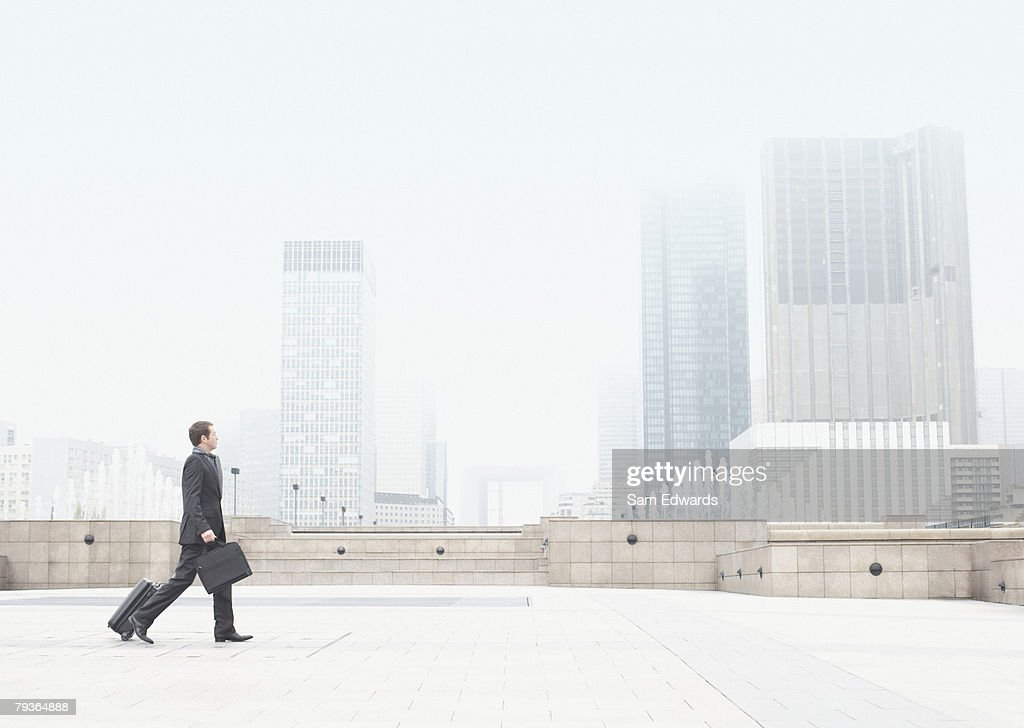 Businessman outdoors walking with luggage : Stock Photo