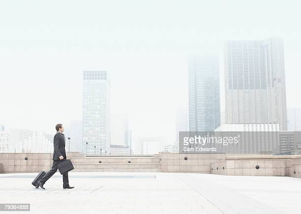 Businessman outdoors walking with luggage
