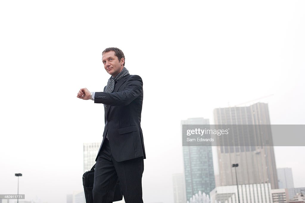 Businessman outdoors with briefcase checking the time : Stock Photo
