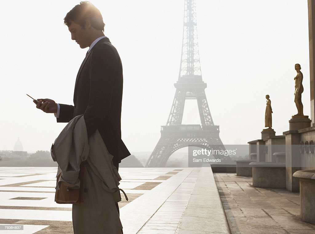 Businessman outdoors with cellular phone by Eiffel Tower : Stock Photo
