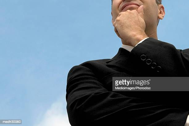 Businessman outdoors with hand on chin, low angle view, close-up, midsection