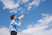 Businessman outdoors with megaphone