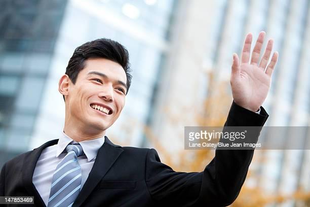 A businessman outside office buildings waving