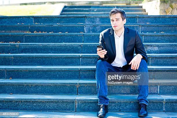 Geschäftsmann auf Handy vor Büro