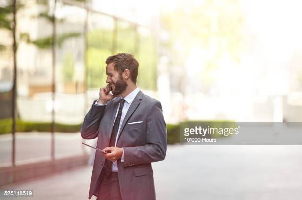 A businessman outside on the phone smiling