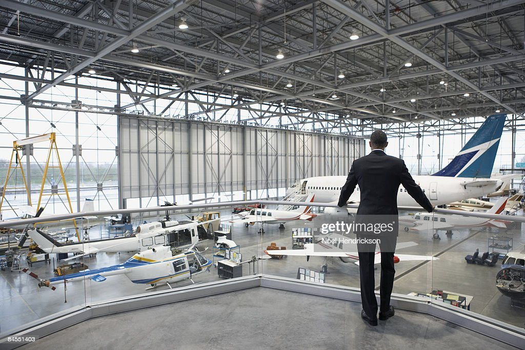 Businessman overlooking hangar of aircrafts