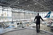 Businessman overlooking hangar of aircrafts