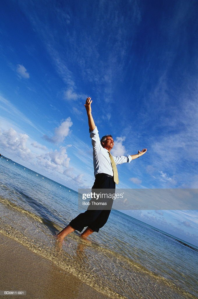 Businessman paddling in sea, arms raised