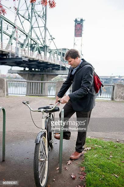 Businessman parking bike in city with bridge behin
