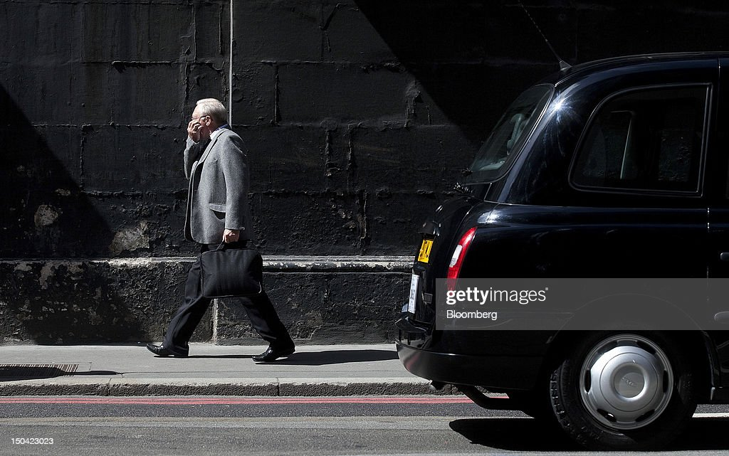 A businessman passes a London taxi cab in London, U.K., on Friday, Aug. 17, 2012. Banks, insurers and other financial-services firms may eliminate a total of about 3,000 jobs across greater London as companies in the New York region add 9,000, according to U.K.-based researcher Oxford Economics Ltd. Photographer: Simon Dawson/Bloomberg via Getty Images